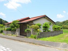 田んぼに囲まれた赤い屋根の平屋
