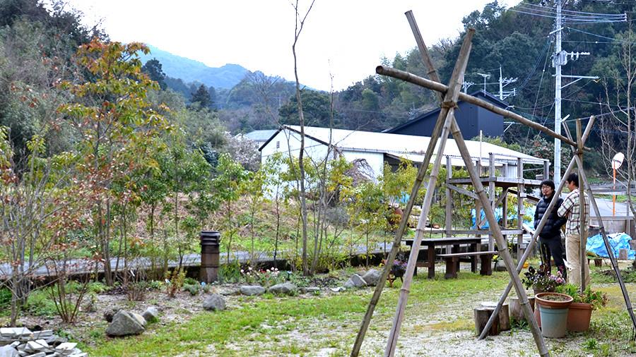 広い庭には手作りの物干し台や遊具。前には山がひろがる。